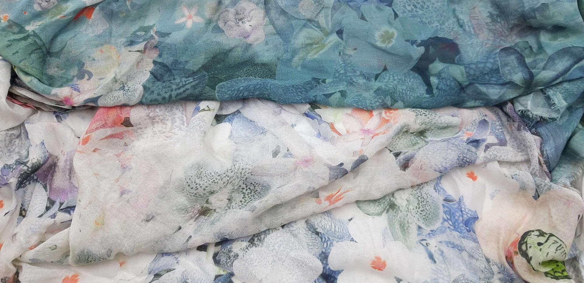 Fular en tonos grises, crudos y verdes. Estampado de dibujos de flores blancas pequeñas y de mariposas. 85% modal 15% seda. 140 cm X 130 cm