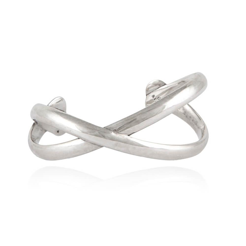 Brazalete con forma de cruz plateada. Metal bañado en plata.