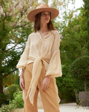 Camisa en color beig, confeccionada en brillante velo de algodón con frunces. Su espalda es más larga y sus lados largos en la parte delantera le permiten atarla o jugar con largos.