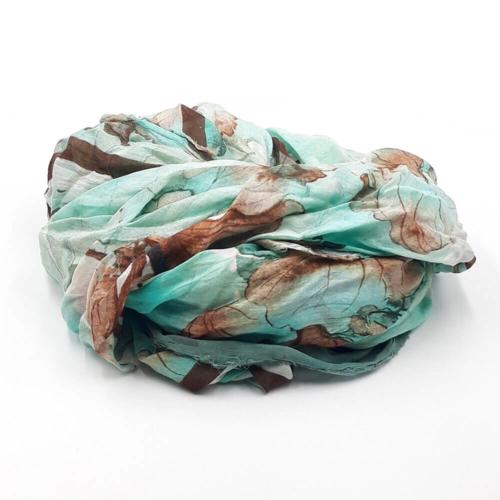Fular en tonos marrones, verdes esmeraldas y estampado de flores marrones. 85% modal 15% seda. 140 X 130 cm.