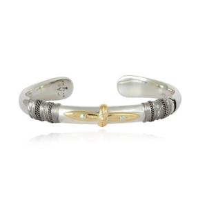 Pulsera abierta envuelta en hilos metálicos y centro adornado con cruz frontal bañada en oro. Metal bañado en plata y oro.