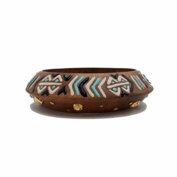 Brazalete de madera. Un lado con incrustaciones de piezas bañadas en oro y el otro lado pintado a mano con motivos geométricos y étnicos.