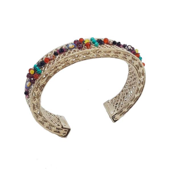 Brazalete ajustable cosido con lentejuelas, anyolita, ónix, jade teñido de amarillo, turquesa, cornalina, granate, perlas japonesas y cristal de Swarovski. Metal bañado en oro 14k.