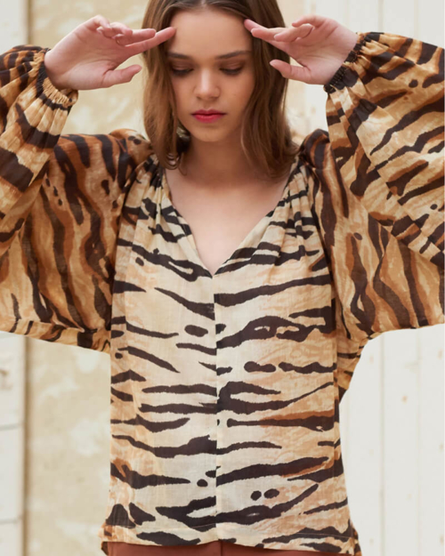 Blusa de manga larga con estampado de tigre. Los frunces a lo largo del escote y alrededor de los puños crean volúmenes voluptuosos.