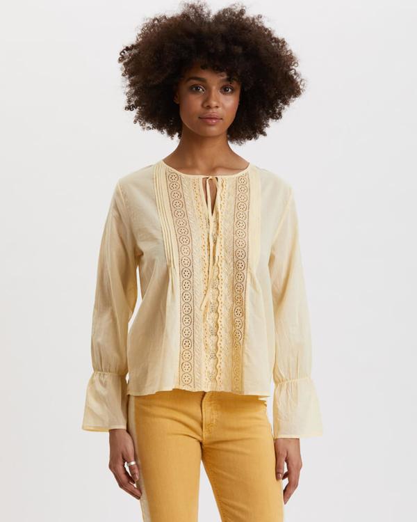 Blusa de manga larga con volante, en color amarillo claro. Adornada con puntilla floral.