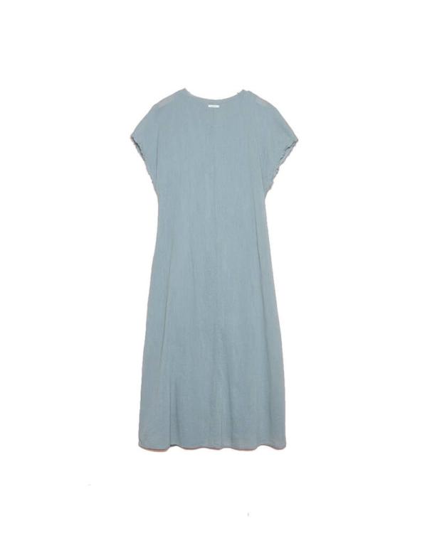 Vestido largo holgado en azul lavanda, de manga corta con un corte diagonal desde el hombro hasta la cintura por la parte delantera. El cuello es redondo y forro interior.