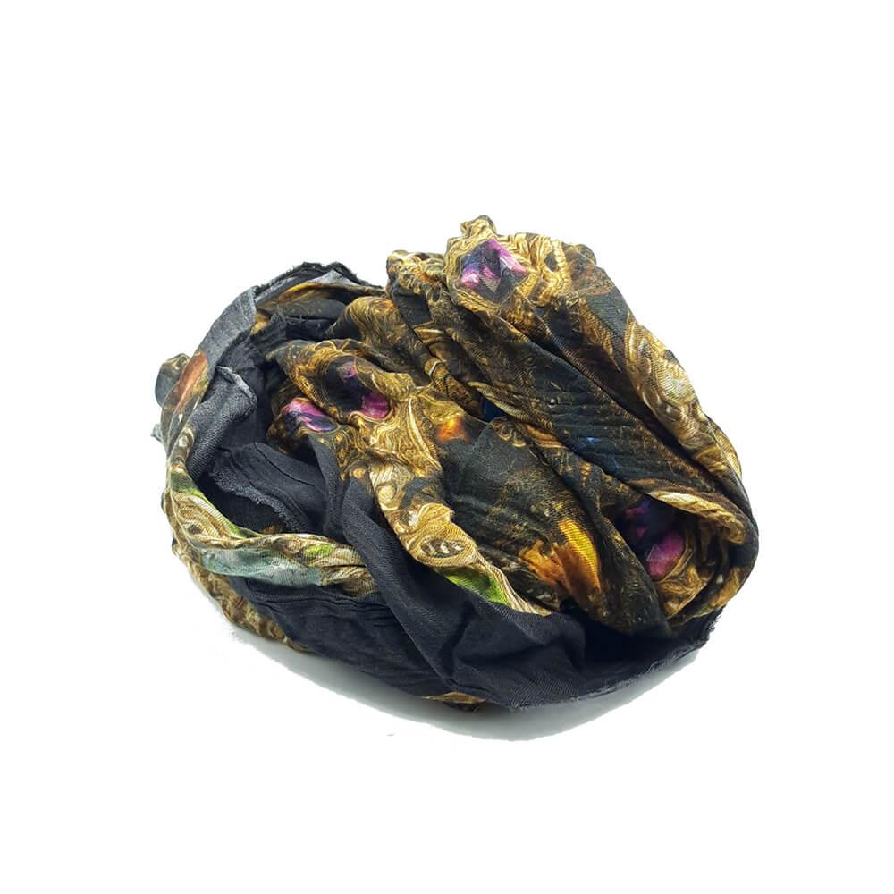 Fular en tonos marengos y dorados, con dibujo de joyas circulares doradas. 90% modal 10% seda. 140cm X 130cm.